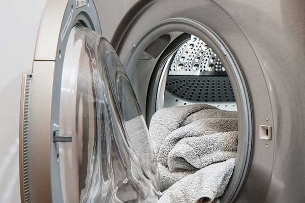 drying machine door open with freshly washed towels inside