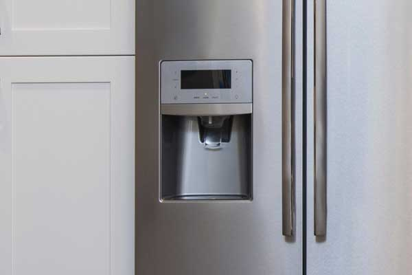 detail of ice maker on modern stainless steel refrigerator appliance