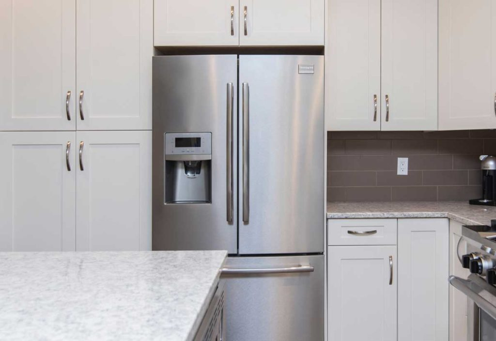 a modern stainless steal fridge with an ice maker in the door