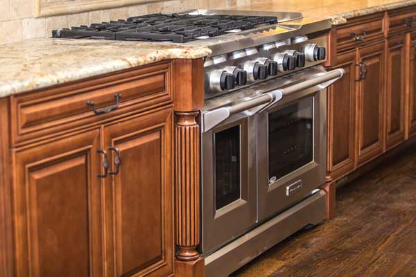 stainless steel oven and stove top between wooden cabinetry