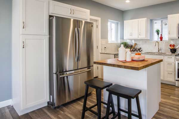 modern kitchen with white cabinetry stainless steel fridge hardwood floors and island with stools