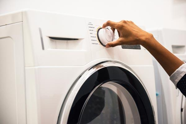 a woman turning the knob on her washing machine