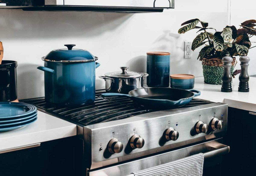 stainless steel oven and stove top with blue dishes and pans on top
