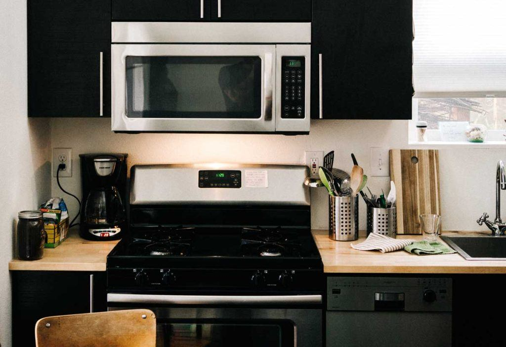 stainless steel oven stove and microwave in modern kitchen with black cabinetry and various items on countertop